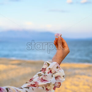 Woman in pink flower dress holding a sea shell over sea and mountains background at the beach in Greece - Starpik Stock