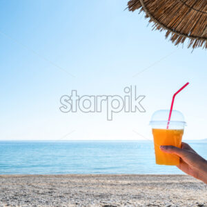 Woman's hand holding a cup with a drink under a umbrella with beach and Aegean sea on the background, Asprovalta, Greece - Starpik Stock