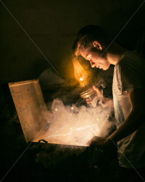Young man in white t-shirt with a lamp in his hand, looking into a chest with smoke and mystical light coming from it. - Starpik Stock