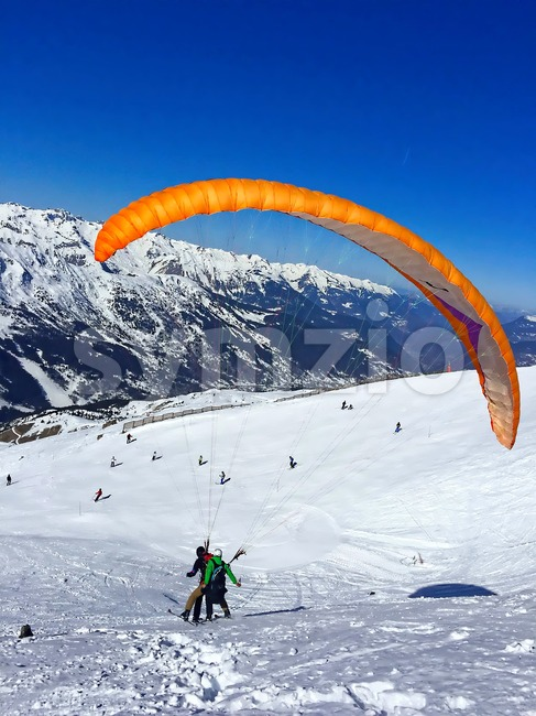 paraglider with instructor over the ski slopes in france alps mountains beautiful courchevel, vertical Stock Photo