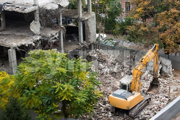 Construction site cran and heavy tractor destroying a building Stock Photo
