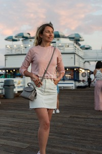 Happy blonde woman in pink sweater at the pier of Malibu, California Stock Photo