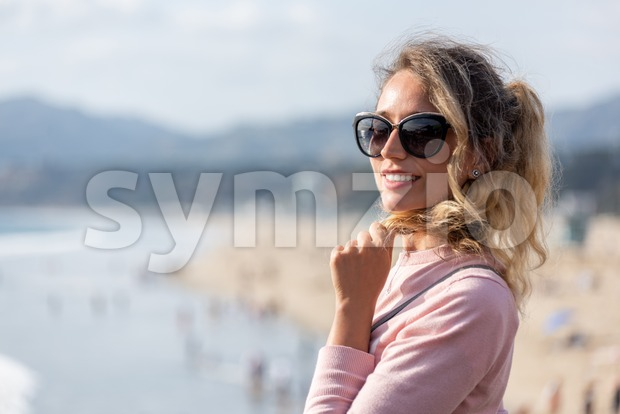Happy blonde woman wearing sunglusses at the beach of Los Angeles, California Stock Photo