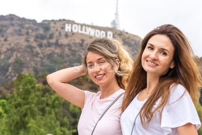 Happy blonde woman at the hollywood mountain in Los Angeles together with best friend, California Stock Photo