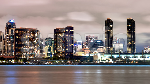 Cityscape of San Diego at night, high and modern buildings, moored boats, Pacific ocean on the foreground Stock Photo