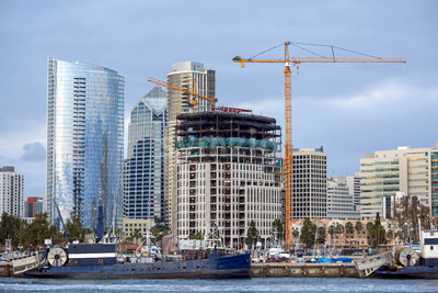 Construction works and high, modern buildings, yachts and two old moored boats on the foreground in San Diego, USA Stock Photo