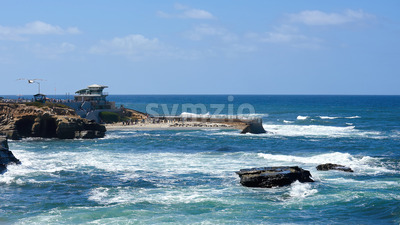 Pacific rocky coast with lots of walking people near the lighthouse in San Diego, USA Stock Photo