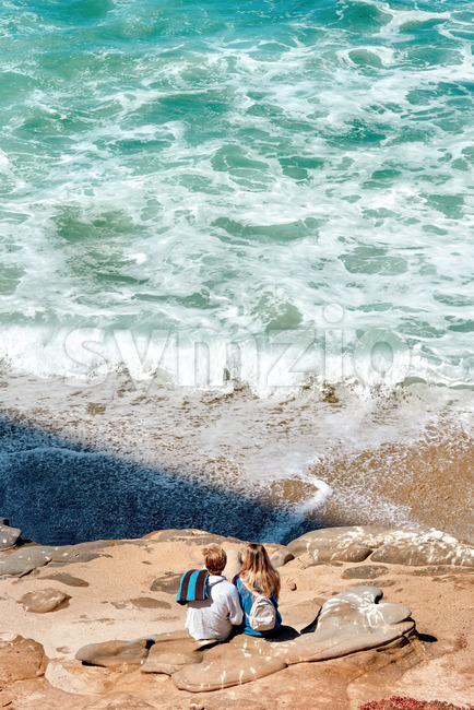 A couple sitting on the rocks near the Pacific ocean in San Diego, USA