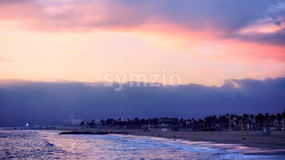 Santa Monica State beach at sunset, waves of the Pacific ocean, walking and relaxing people, Los Angeles, USA Stock Photo