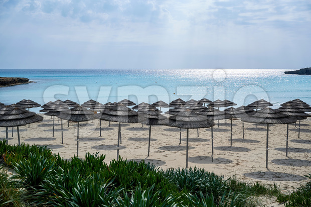 Nissi beach in Ayia Napa full of reed umbrellas and Mediterranean sea in the background Stock Photo