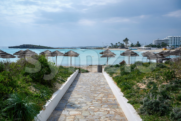 Trail leading to the sea and beach full of reed umbrellas in Ayia Napa Stock Photo