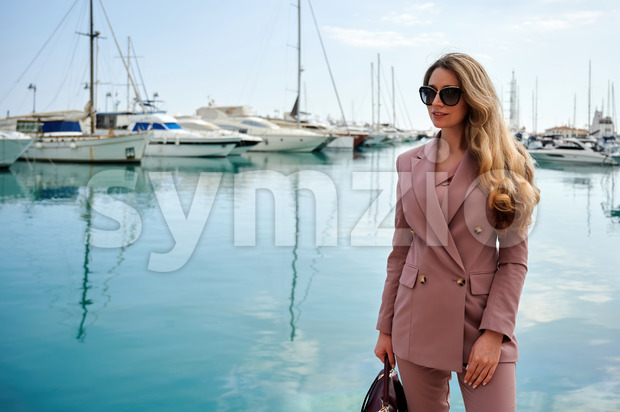 Portrait of a caucasian woman in sunglasses with bag and yachts on the background in Limassol, Cyprus Stock Photo