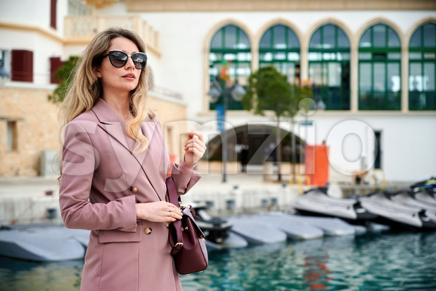 Portrait of a caucasian woman in sunglasses with bag and water channel on the background in Limassol, Cyprus