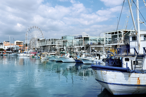LIMASSOL, CYPRUS - FEBRUARY 17, 2020: Moored yachts in the wharf with cafes and Ferris ring on the background Stock Photo