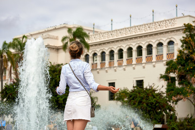 A caucasian woman spreading hands with fountain and building on the background in Balboa Park, San Diego Stock Photo