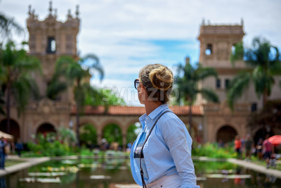 A caucasian woman turned away and looking on the aged building in Balboa Park, San Diego Stock Photo