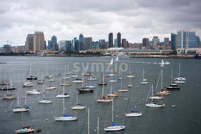 Multiple moored yachts with high modern buildings on the background in San Diego Stock Photo