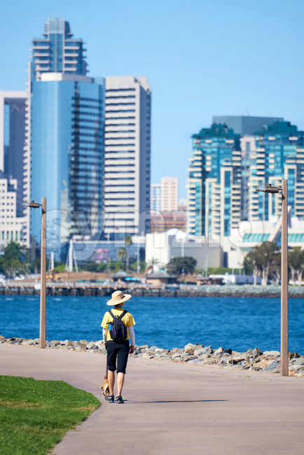 Woman with round classic hat walking the dog in waterfront park. San Diego, California Stock Photo