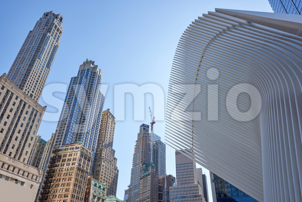 Wide shot of the World Trade Center station in New York with lots of high modern and aged buildings in the background. Stock Photo
