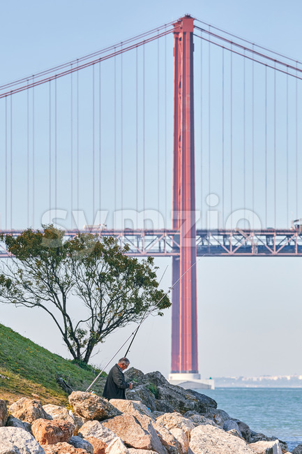 LISBON, PORTUGAL - OCTOBER 25 2019: Vertical shot of a fisherman occupied by a lovely deal and staying near the water with Ponte 25 de Abril bridge Stock Photo