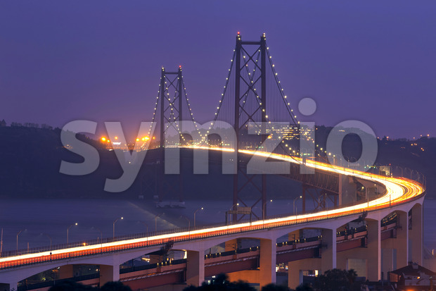 Shot of the huge Ponte 25 de Abril bridge in Lisbon Portugal taken at dusk towering above the chanel with multiple light tracks of many cars passing Stock Photo