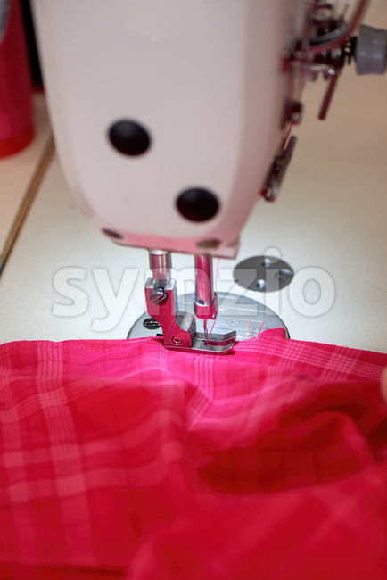 Woman working on a sewing machine. Red cloth Stock Photo