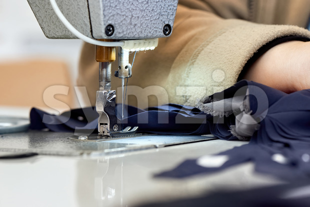 Woman working on a sewing machine. Blue cloth Stock Photo