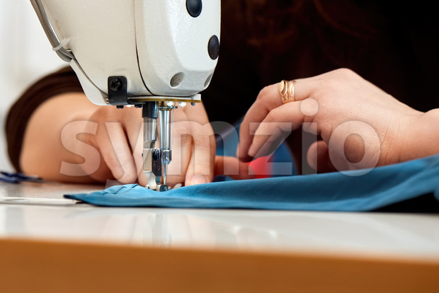 Woman working on a sewing machine with blue cloth Stock Photo
