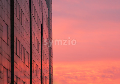 the colorful sky during sunset is reflected in the windows of the building, Bucharest, Romania Stock Photo