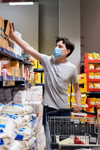 Young man with a protective medical mask taking sugar from the supermarket's shelves near the cart. Corona Virus idea Stock Photo