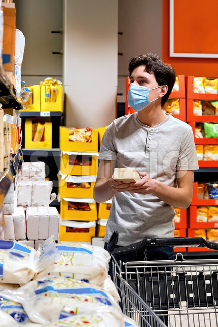 Young man with a protective medical mask looking for sugar at the supermarket's shelves near the cart. Corona Virus idea