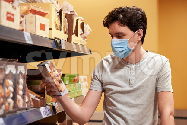 Young man with a protective medical mask looking at the snacks from the shelves in a supermarket. Corona Virus idea
