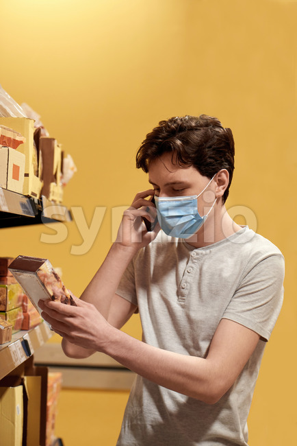 Young man with a protective medical mask talking on the phone while looking at the snacks from the shelves in a supermarket. Corona Virus idea Stock Photo