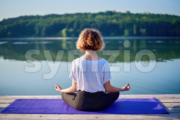 A young woman with curly hair doing yoga on a pier near a lake with green trees on the background Stock Photo