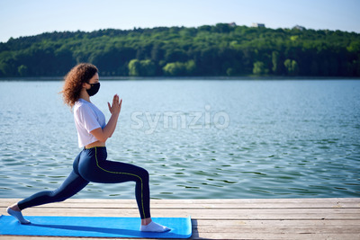 A young woman with curly hair and in medical mask doing yoga on a pier near a lake with green trees on the background Stock Photo