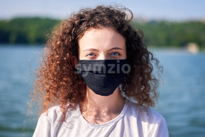 Portrait of a young woman with curly hair in medical mask near a lake with green trees on the background Stock Photo