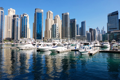Dubai marina cityscape at daylight. Yachts parked in port on foreground Clear sky. United Arab Emirates Stock Photo