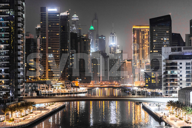 Modern looking view in Dubai at night, United Arab Emirates. Bright lights with orange predominance on the building Stock Photo