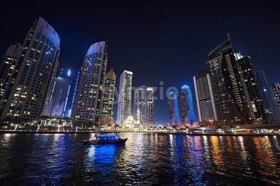Dubai Marina at night with colorful touristic boats cruising on water. United Arab Emirates Stock Photo