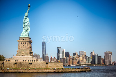 NEW YORK, USA - SEPTEMBER 19, 2019: Statue of Liberty with lots of people near it and Manhattan on the background. Vibrant colors Stock Photo