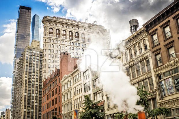 NEW YORK, USA - SEPTEMBER 19, 2019: Block of flats with skyscrapers and Flatiron Building on the background. Vibrant colors Stock Photo