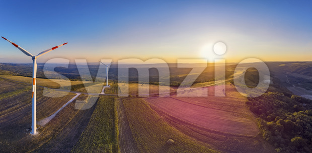 Panorama of wind turbine in a windfarm on hills in Moldova at sunset, aerial drone view with glowing sun Stock Photo