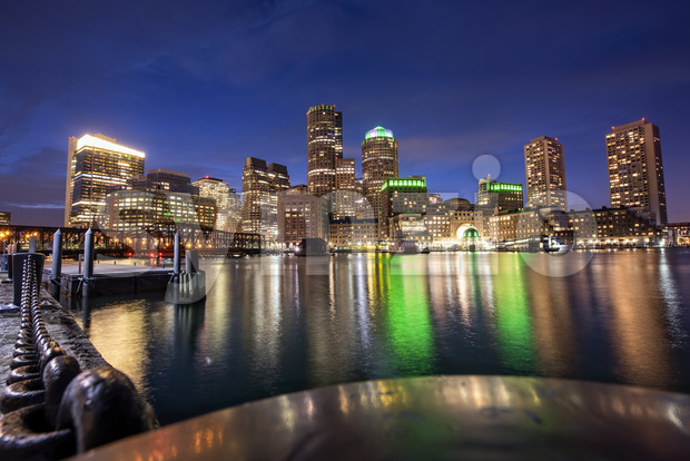City of Boston with buildings and port at night, water reflections and blue sky with stars