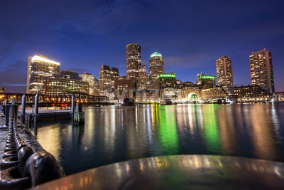 City of Boston with buildings and port at night, water reflections and blue sky with stars Stock Photo
