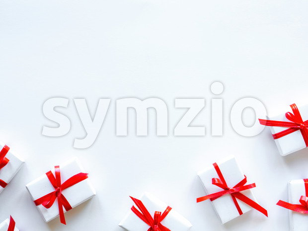 Few gift boxes with red tape on white background. Holiday concept. Top view