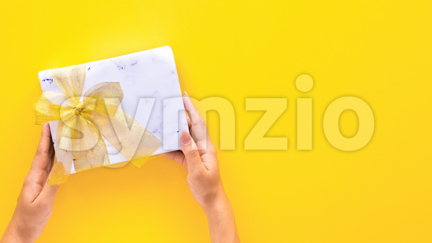 Female hold holds a gift box on yellow background. Holiday concept. Top view Stock Photo
