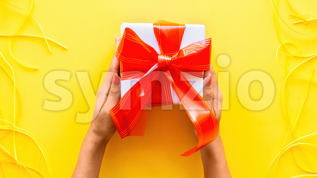Female hands hold a gift box, tapes around on yellow background. Holiday concept. Top view Stock Photo