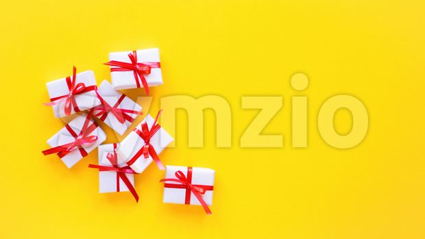 Few gift boxes with red tape on yellow background. Holiday concept. Top view Stock Photo