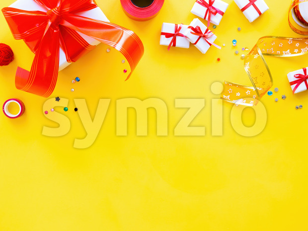 Few gift boxes with red tape, decoration around on yellow background. Holiday concept. Top view