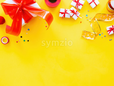 Few gift boxes with red tape, decoration around on yellow background. Holiday concept. Top view Stock Photo